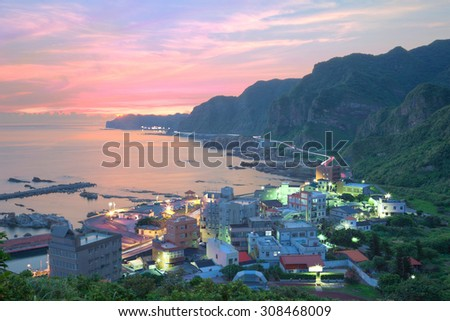 Aerial view of a fishing village and Coast Highway at dawn on northern coast of Taipei Taiwan ~ Beautiful coastal scenery under moody rosy sunrise sky Cliff coastal line  road at Dawn ~ - stock photo