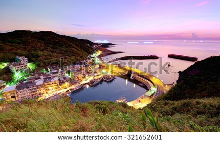Aerial view of a fishing village at dawn on northern coast of Taipei Taiwan ~ Beautiful coastal highway crossing the harbor of a fishing village under dawning sky - stock photo