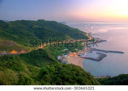 Aerial view of a fishing village at dawn on northern coast of Taipei Taiwan ~ Scenery of a coast highway along beautiful coastline and a fishing village in golden sunlight - stock photo