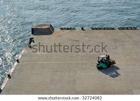 Aerial view of a fork lift manoeuvring in the dock - stock photo