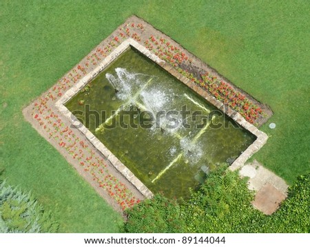 aerial view of a fountain in a pond surrounded by grass