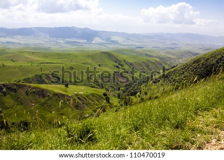 Aerial view of a green landscape under blue sky - stock photo