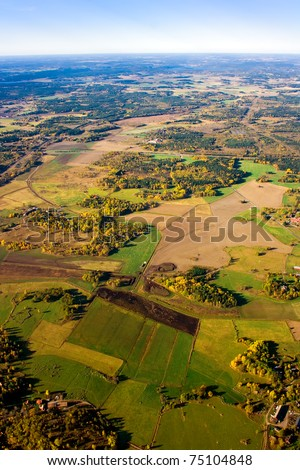 Aerial view of a green rural area under blue sky in autumn - stock photo