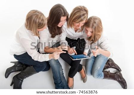 Aerial view of a group of amused girls around a pc tablet.  Please note that the logo and writing on the tablet are mine. I am attaching a property release, so no copyright issue. - stock photo