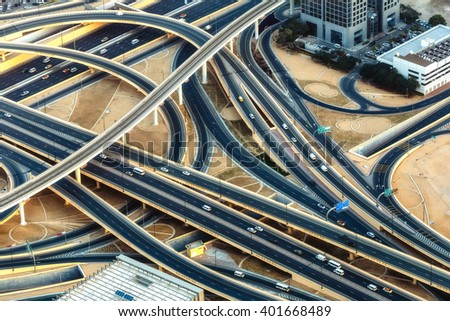 Aerial view of a highway intersection with traffic in Dubai, UAE, at sunset. Famous Sheikh Zayed road in Dubai downtown. Transportation and driving concept. - stock photo