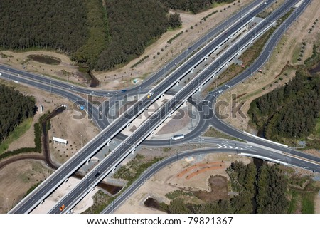 Aerial view of a Highway Junction Interchange with roundabout beneath. An example of civil engineering and road infrastructure. - stock photo