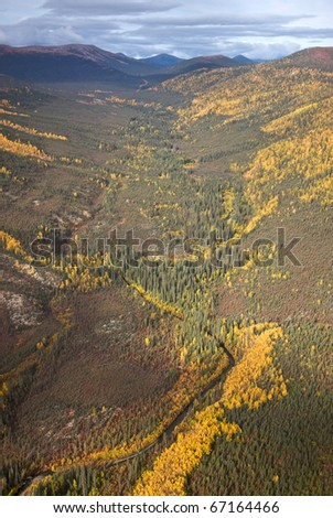 Aerial view of a mountain valley with a small river cutting through. - stock photo