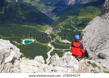 Aerial view of a mountaineer above Val Gardena valley, Dolomite Alps, Italy - stock photo