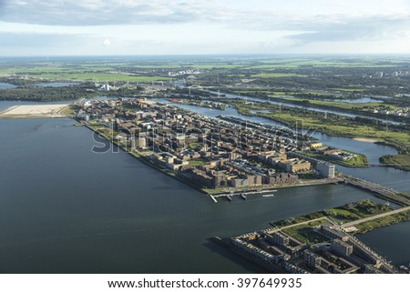 Aerial view of a new district in Amsterdam IJburg, Netherlands with a lot of colorful houses. In the front of the picture the Steigereiland and the river IJ. - stock photo