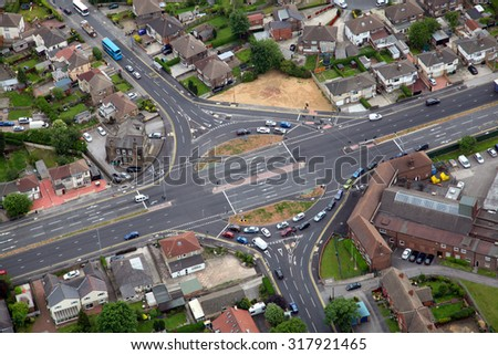 aerial view of a newly built road junction roundabout with traffic, UK