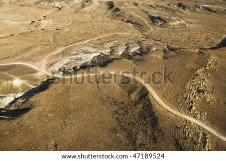 Aerial view of a of rural, desert landscape with a road running through it. Horizontal shot. - stock photo