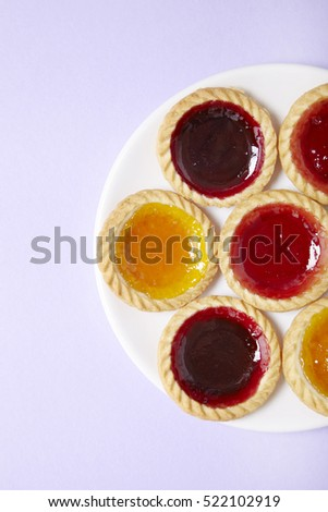 Aerial view of a plate full of assorted fruit jam tarts on a pastel purple background