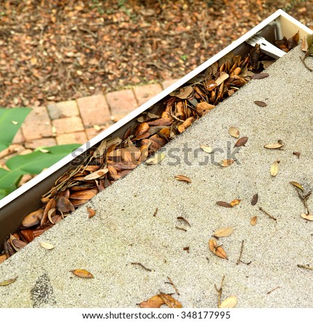 Aerial view of a roof top gutter clogging with leaves