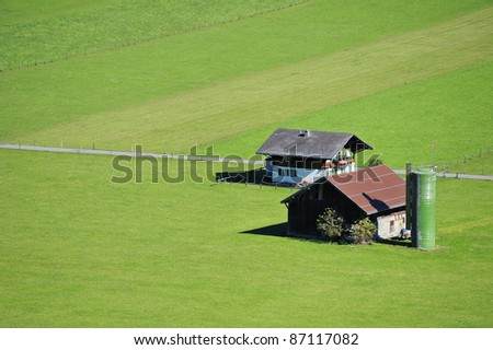 Aerial view of a small farm in Switzerland, set in green fields. Space for text on the green of the fields.