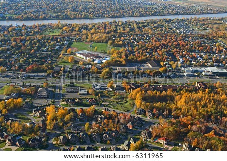 Aerial view of a suburban neighborhood in bright colors of autumn. - stock photo