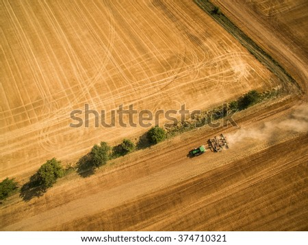Aerial view of a tractor working a field after harvest - stock photo