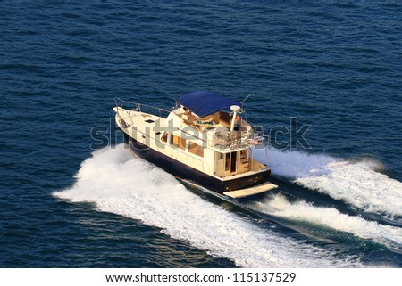 Aerial view of a yacht with splash and wake - stock photo