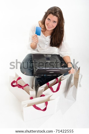 Aerial view of a young brunette holding a card using her computer surrounded by shopping bags - stock photo