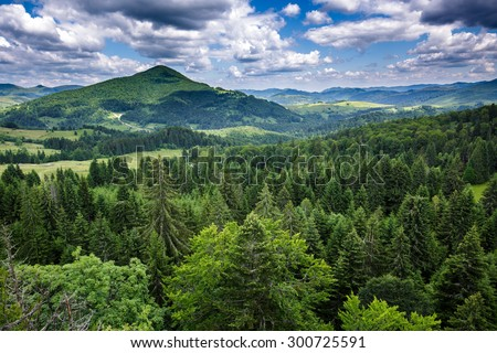 Aerial view of afforested mountains under a cloudy sky - stock photo
