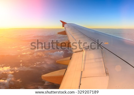 Aerial view of airplane flying above shade clouds and sky from an airplane fly during the sunset. View from the plane window of emotional moment during international travel around the world.  - stock photo