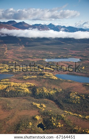 Aerial view of an Alaskan landscape with lakes and mountains in the background. - stock photo