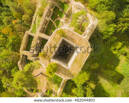 Aerial view of ancient ruins (gothic castle Gutstejn) in a deep forest. Discovery landmarks from drone. Czech Republic, Europe.