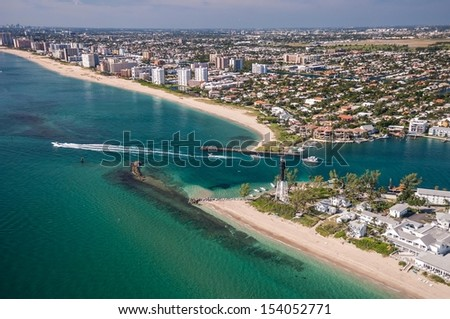 aerial view of beach and boaters at hillsboro inlet on atlantic ocean in florida with lighthouse - stock photo