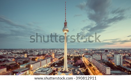 Aerial view of Berlin skyline with famous TV tower and dramatic clouds in twilight during blue hour at dusk with retro vintage Instagram style nostalgic pastel toned filter effect, Germany - stock photo