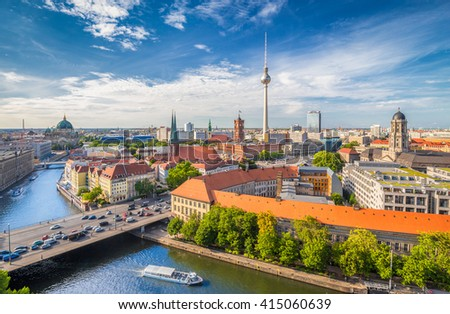 Aerial view of Berlin skyline with famous TV tower and Spree river in beautiful golden evening light at sunset on a sunny day with blue sky and clouds in summer, Germany - stock photo