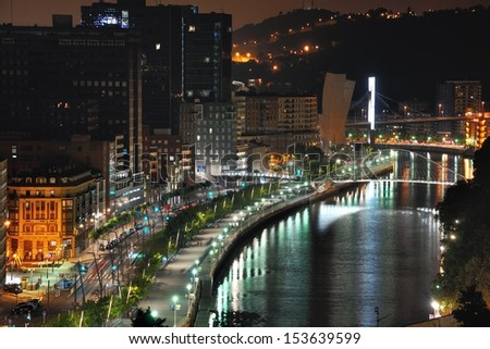 Aerial view of Bilbao, Spain city downtown with a Nevion River and promenade at Night. It is a capital of province of Biscay, a very large city and a popular touristic destination.