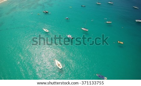 Aerial view of Blue turquoise Ocean waters of the Caribbean Sea surrounded by boats, yachts and Boutique Hotels in the Distance