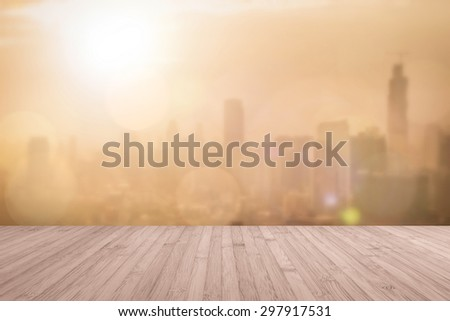 Aerial view of blurred abstract background of morning sunrise with flare from the kitchen balcony with wood floor in red brown color tone: Wooden table with blur cityscape view with gold light