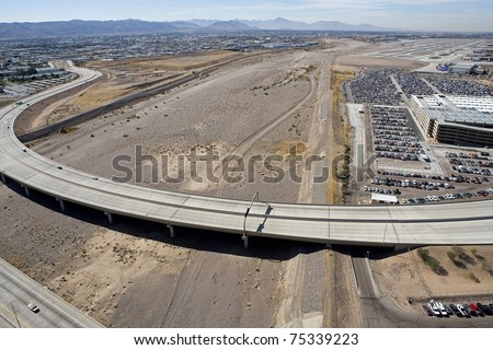 Aerial view of bridge over dry Salt River bottom next to busy Sky Harbor Airport and long term parking in Phoenix, Arizona - stock photo