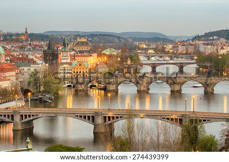 Aerial view of Bridges in Old Town of Prague (Czech Republic). Beautiful city lights over Vltava river in the sunset. - stock photo