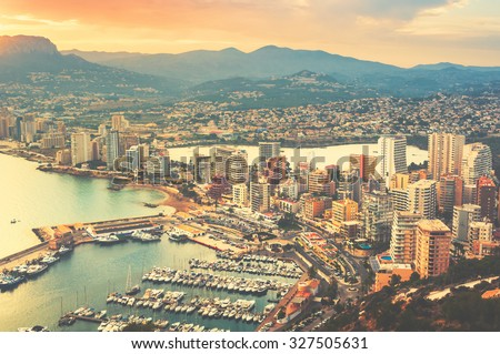 Aerial view of Calpe, Costa Blanca at sunset. Popular summer resort in Spain with mediterranean sea and Las Salinas lake, mountains at the background, skyscrapers. Toned photo - stock photo