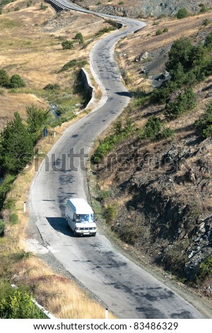 aerial view of car crosses a mountain road in southeastern of Albania - stock photo
