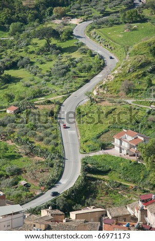 aerial view of cars are going through a winding rural road - stock photo