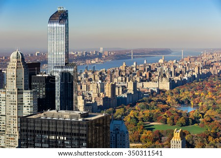 Aerial view of Central Park in autumn with Upper West Side in Manhattan, New York City. The view includes Midtown skyscrapers, the Hudson River and the George Washington Bridge. - stock photo
