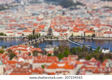 Aerial view of Charles Bridge over Vltava river and Old city from Petrin hill Observation Tower with tilt shift toy effect shallow depth of field. Prague, Czech Republic - stock photo