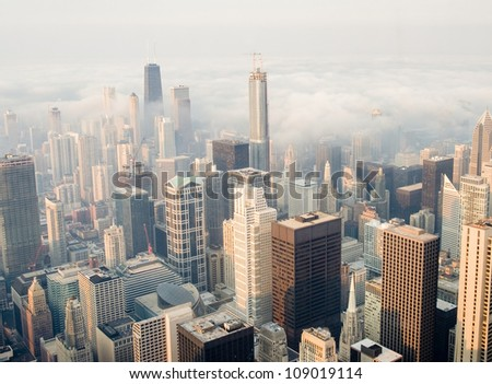 Aerial view of Chicago city skyline with downtown buildings covered partially with rolling thunder clouds