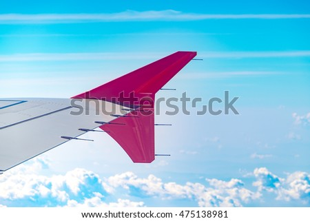 Aerial view of cloud and sky and land with airplane wing from airplane window ,Traveling concept.