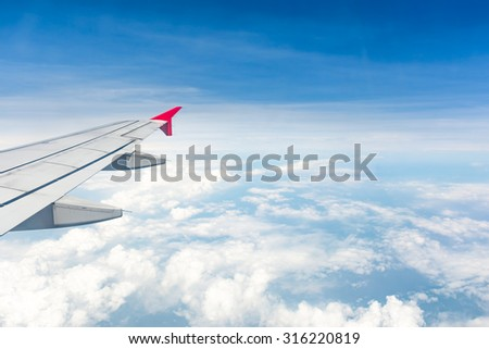 Aerial view of cloud  blue sky and plane wing view through the airplane  window. - stock photo