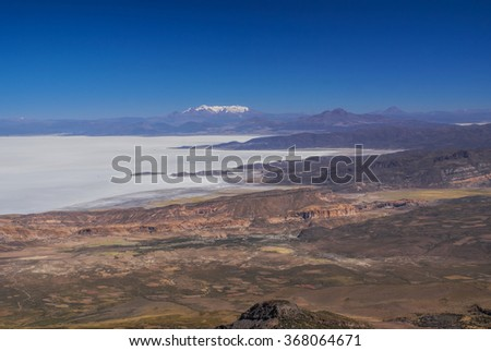 Aerial view of colored mountains and salt plane Salar de Uyuni in Bolivia - stock photo