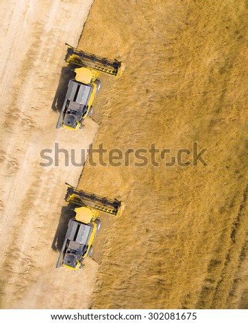 Aerial view of combine harvester on wheat field. Industrial background on agricultural theme. - stock photo