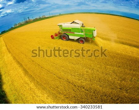 Aerial view of combine on harvest field. Colorful photo. Wide angle shot. - stock photo