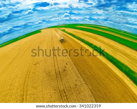 Aerial view of combine on harvest field. Wide angle shot. - stock photo