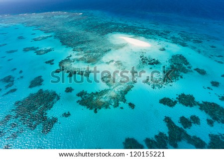 Aerial view of coral sand cay and Great Barrier Reef with clear blue water, Queensland, Australia - stock photo