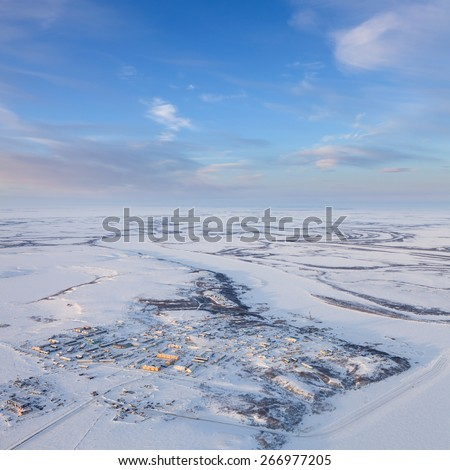Aerial view of countryside is beside the village and the tundra river during cold winter day. - stock photo