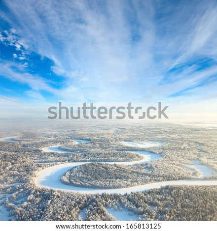 Aerial view of countryside road which is near forest river during cold winter day. Magnificent hoarfrost is on trees.  A winter forest is in a hard frost. - stock photo