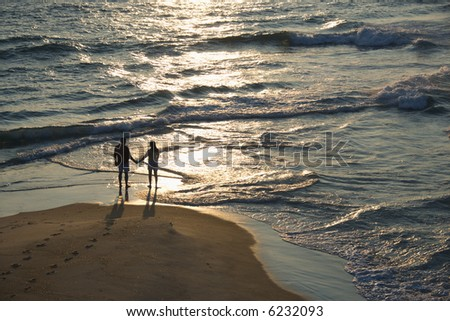 Aerial view of couple holding hands on beach in Bald Head Island, North Carolina at sunset. - stock photo